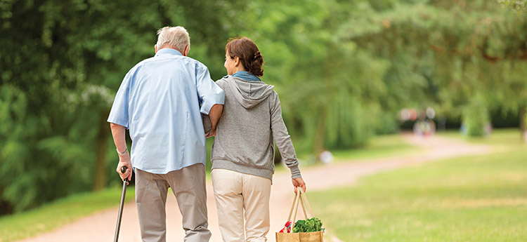 A caregiver is assisting an older man walk